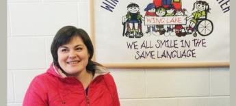 """A smiling woman looks off in the distance. Behind her is a sign that says """"We all smile in the same language"""" with images of children with and without disabilities."""