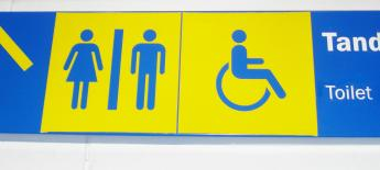 "Blue and yellow sign indicating lavatory. Text reads ""Tandas - Toilet"""