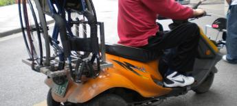 Wheelchair strapped to the back of a motor scooter.