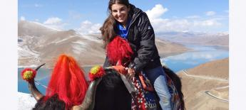 A young woman sits atop a wooly yak with a lake and mountains in the background.