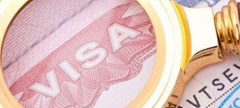 """A magnifying glass is held to a document labeled """"visa."""""""