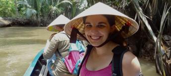 Emily block wears a Vietnamese-style hat while riding in a boat on a river.