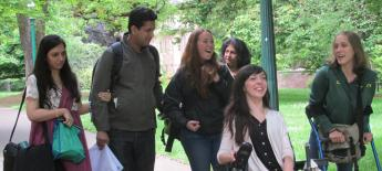 A group of young Americans and exchange students with and without disabilities talk while walking through a college campus.