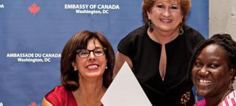 Two women present a third women with a special award certificate.
