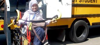 A high school girl wearing a headscarf and sitting in a wheelchair rides the lift to board a yellow school bus.