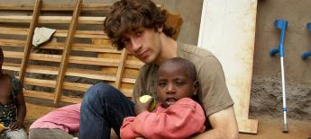 Zach sits on the ground with Ugandan child with a disability