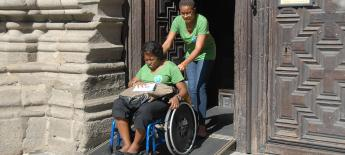 Woman in a manual wheelchair gets assistance down a ramp outside a carved wooden door