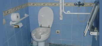 Accessible western style toilet with a grab bar and space next to the toilet where foldable mounted shower chair pulls down with handheld shower hose