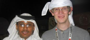 A Bahraini man in cultural dress stands with an American man.