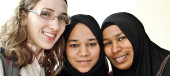 Young American with learning disability smiles with two Muslim women during a cultural exchange
