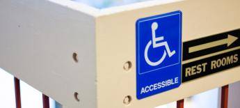 Wheelchair access sign with restroom arrow