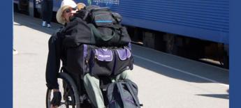 A man pushes himself in his manual wheelchair with luggage on top his lap at a Swedish train station