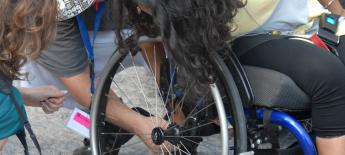 Three people, including the wheelchair user, lean over to check out the axel of her manual wheelchair