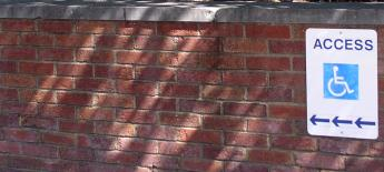 The sign with the symbol for wheelchair access is posted on a brick wall outside of a building.