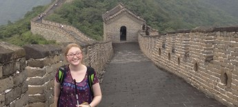 A young white woman stands with a white cane atop the Great Wall of China