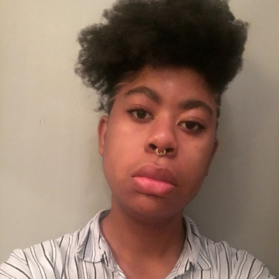Gillian Giles a non binary black person with short  afro hair and a septum ring looking straight forward. They are in front of a grey wall and are wearing a light blue collared shirt with stripes.